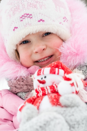 Closeup portrait of happy child holding Christmas decoration in winter photo