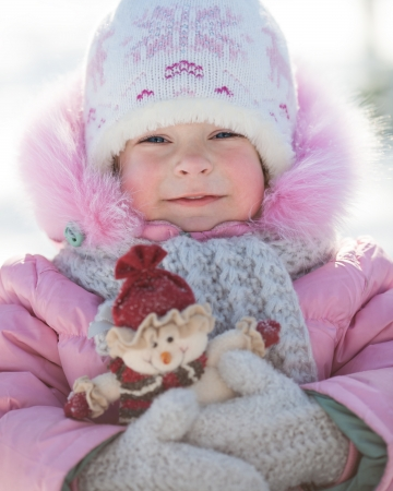Happy smiling child holding snowman in winter park photo