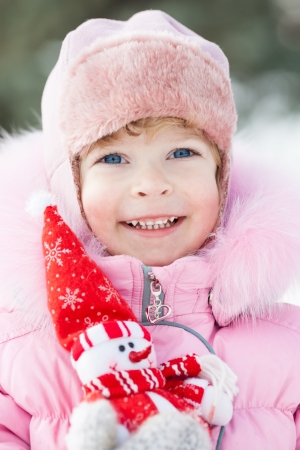 Happy smiling child with Christmas snowman in winter park photo