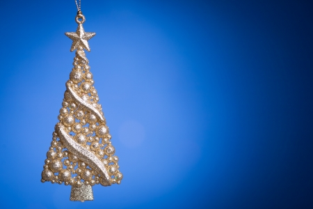 with copy space: Golden Christmas tree against dark blue background