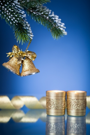 Christmas tree decorations and burning candles against blue background photo