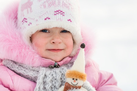 Happy child with snowman in winter park photo