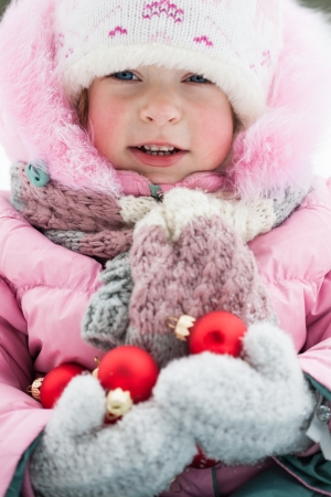 Happy child holding Christmas decorations in winter park  Outdoors shot photo