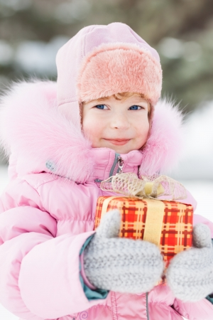 Happy child holding Christmas gift in winter park. Outdoors shot photo