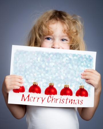 Happy child holding photo of Christmas tree decorations  photo