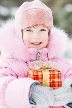 Happy smiling child with Christmas gift in winter park photo