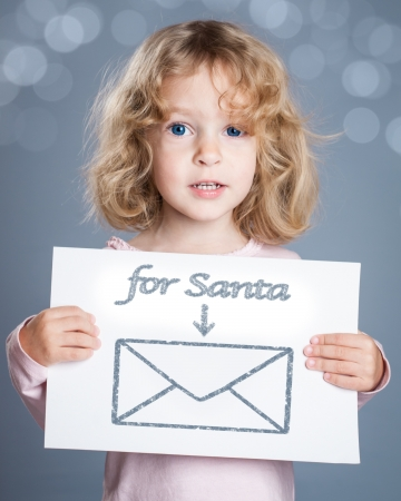 Happy child holding Christmas card with hand drawn letter for Santa Claus and gift photo