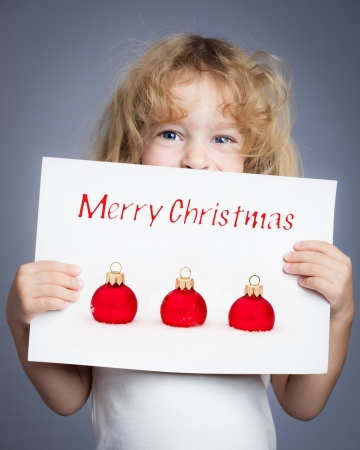 Happy child holding Christmas card photo