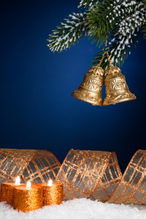 Christmas tree decorations and burning candles in snow against blue background