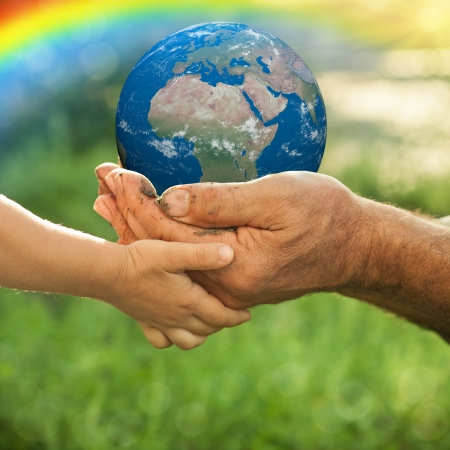 Earth in hands of old man and child against green spring background  Ecology concept Stock Photo