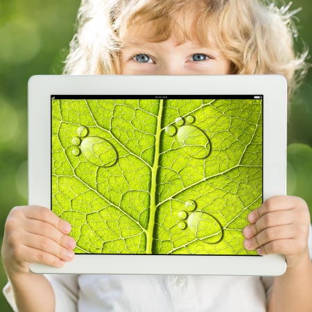 greenhouse effect: Happy child holding tablet PC with photo of green leaf texture outdoors in spring  Ecology concept Stock Photo