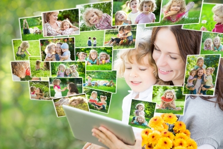 family photo: Happy family using tablet PC outdoors in spring park Stock Photo