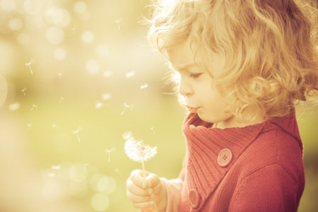 Beautiful child blowing away dandelion flower in spring photo