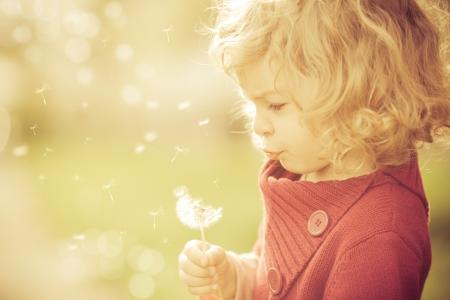 sogno: Bel bambino soffiando via fiori di tarassaco in primavera