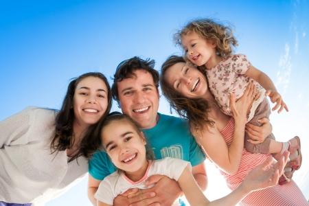 uomo felice: Gruppo di persone sorridenti felici contro il cielo blu, angolo, vista dal basso, fisheye sparare