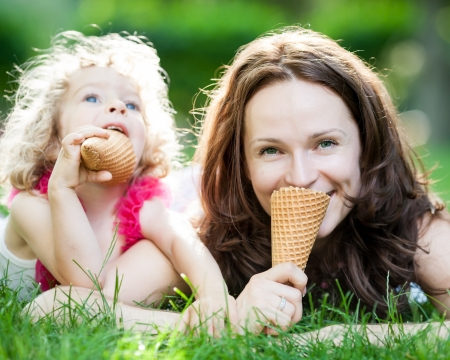 Happy family eating ice-cream outdoors in spring park against blurred green background photo