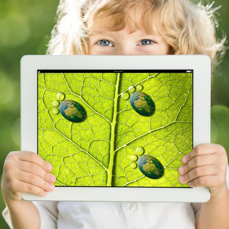 Happy child holding tablet PC with photo of green leaf texture outdoors in spring  Ecology concept photo