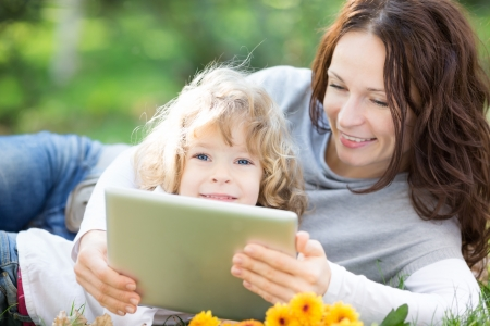 Happy family using tablet PC against green spring background photo