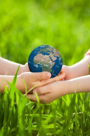 children's: Earth in children s hands against green spring background Stock Photo