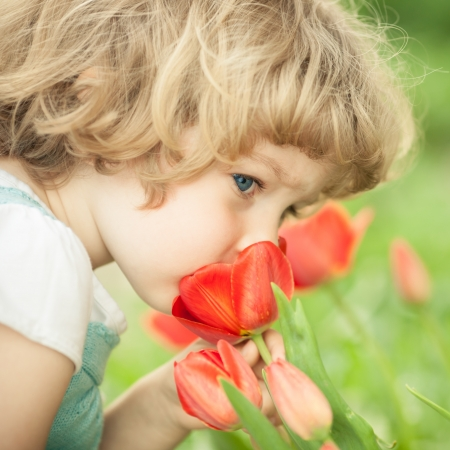 Child smelling tulip flower in spring outdoors photo