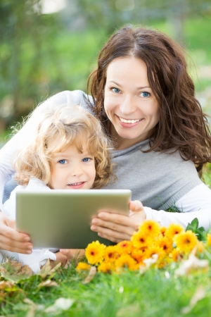 pads: Happy family using tablet PC against green spring background