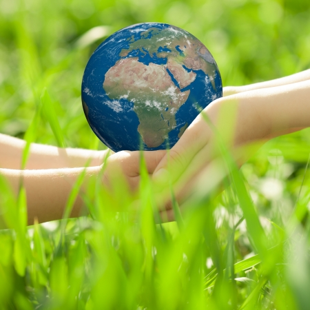Earth in children s hands against green grass blurred background photo