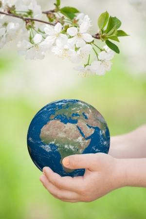 children s: Earth in children s hands against green spring background Stock Photo