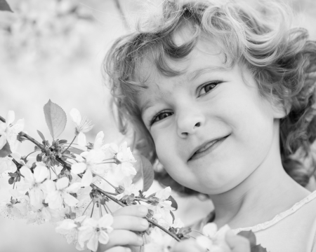 Happy child holding spring flower  Black and white, shallow depth of field photo