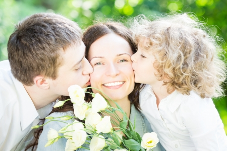 Happy family having fun outdoors in spring park against nature green background. Mother`s day concept photo