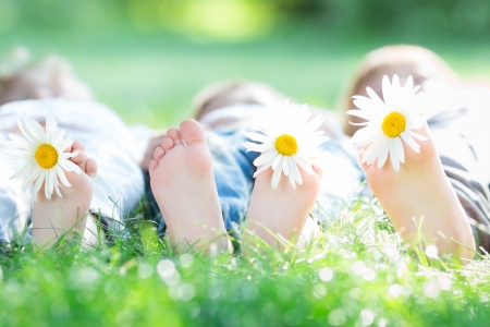 Group of happy children lying outdoors against green spring background Stock Photo