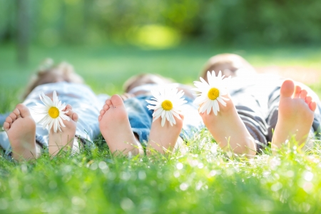 kids feet: Group of happy children with flowers lying outdoors in spring park