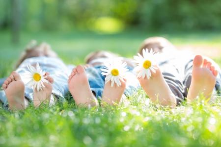 pie bebe: Grupo de niños felices que mienten al aire libre con las flores en la primavera de parque
