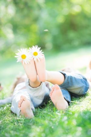 lying in grass: Grupo de ni�os felices jugando al aire libre en el parque del resorte