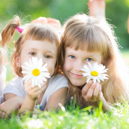 Happy children with flowers lyying on grass against green spring background photo