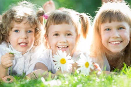 family grass: Group of happy children playing outdoors in spring park Stock Photo
