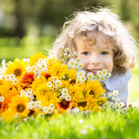 Happy smiling child with big bouquet of spring flowers lying on green grass