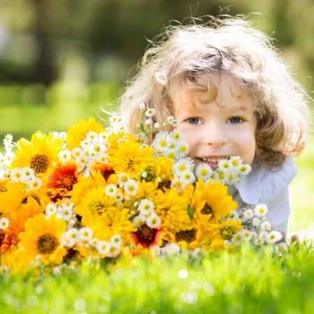 Gelukkig lachende kind met grote boeket van lentebloemen liggend op het groene gras Stockfoto