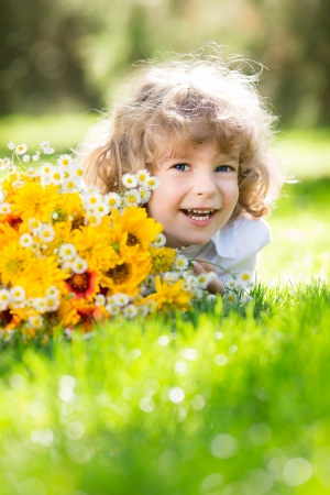 Happy child with bouquet of spring flowers lying on green grass