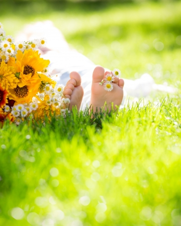relaxation exercise: children`s feet with spring flower on green grass