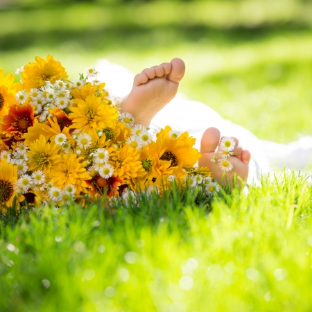 children`s feet on spring flower against green grass background Stock Photo - 17347804