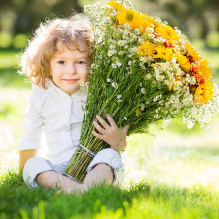 Happy child with bunch of flowers sitting on green grass in spring park Stock Photo