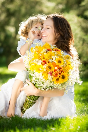 Happy child and woman with bouquet of spring flowers sitting on green grass. Mother`s day concept