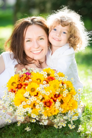 children day: Happy child and woman with bouquet of spring flowers lying on green grass. Mother`s day concept