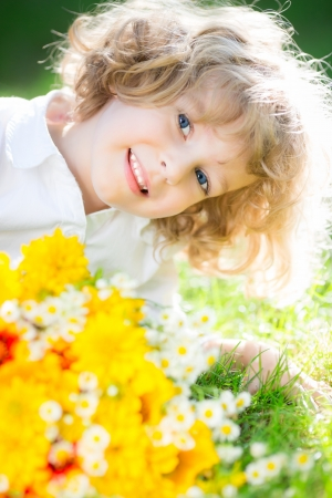 Happy smiling child with yellow spring flowers lying on green grass photo