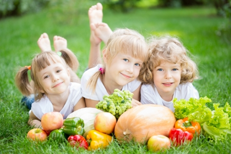 beautiful salad: Group of happy children with fruits and vegetables lying on green grass in spring park  Healthy lifestyles concept Stock Photo