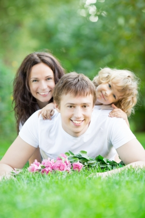Happy family lying on grass in spring park against blurred green background Stock Photo - 17347873