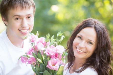 Happy couple with flowers in spring park photo