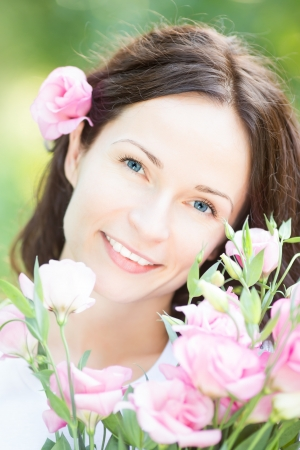 Happy smiling woman with beautiful flowers against green spring background Stock Photo - 17482453