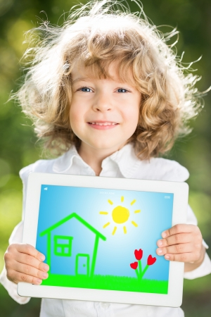Happy smiling child holding tablet PC against green spring background photo