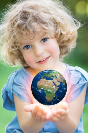 Earth in children`s hands against green spring background. Elements of this image furnished by NASA photo